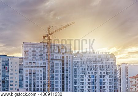 Construction Crane On The Background Of A Newly Built Residential Building With Apartments. Backligh