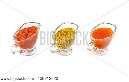 Red Delicious Ketchup Or Tomato Sauce, Adjika And Mustard With Grains In Three Clear Glass Saucepan