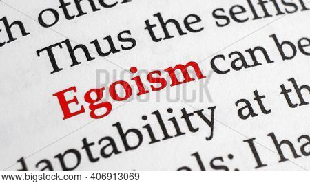 Selective Focus On The Red Word Egoism. Macro Shot Printed Red Colour Word Egoism On A Piece Of Pape