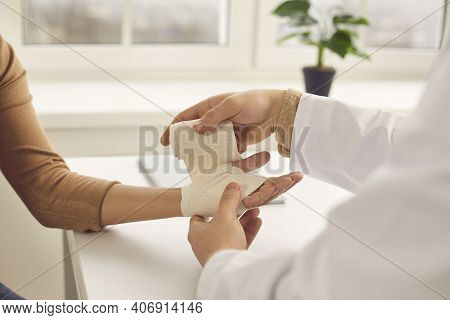 Doctor Gently Rewinds The Patients Hand With An Elastic Bandage In The Medical Office.