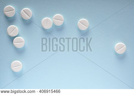 White Pills Lie On A Sheet Of Blue Paper. Close-up. Light Background Or Backdrop On The Theme Of Med
