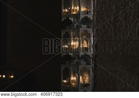 Several Menorahs With Lit Candles, On The First Day Of Hanukkah. Inside A Metal And Glass Installati