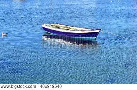 Old Blue Wooden Small Boat Floating On The Sea At Famous Rias Baixas In Galicia Region. Spain.