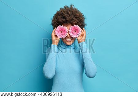 Satisfied Young African American Woman With Curly Hair Covers Eyes With Pink Gerberas Smiles Gently