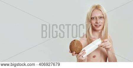 Young Caucasian Man With Long Blond Hair Opening Shampoo Bottle Beside Coconut In Hand While Standin