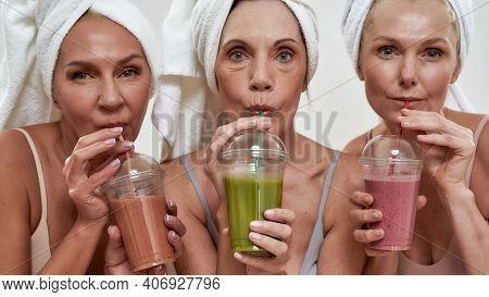 Middle Aged Caucasian Female Friends In Spa Drinking Colorful Smoothies Through Straws While Looking