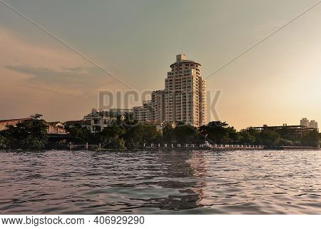 On The Banks Of The Chao Phraya River, There Are City Buildings: New High-rise And Nearby Old Shabby