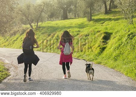 Portrait Of Two Young Women Running At Sunset On Mountain Road Of Umbria Region