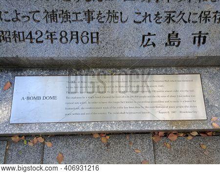 Hiroshima, Japan - April 10, 2018: Memorial Stone Next To The Building A-bomb Dome, Hiroshima. Peopl