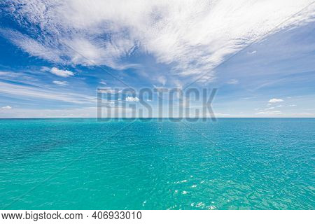 Beautiful White Clouds On Blue Sky Over Calm Sea With Sunlight Reflection In Sea . The Day When The