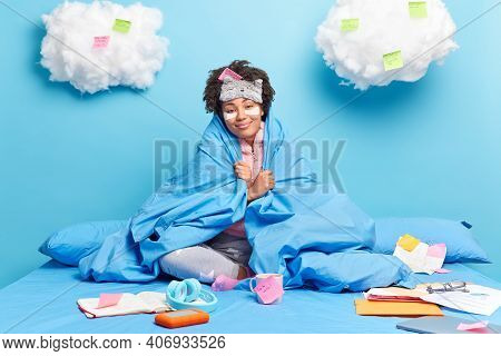 Pleased Afro American Woman Wrapped In Soft Duvet Smiles Pleasantly Enjoys Homey Atmosphere Poses On