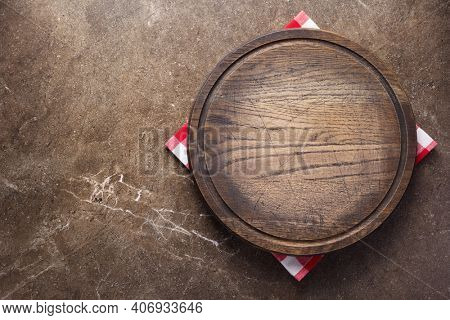 Pizza or bread cutting board and cloth napkin for homemade baking on table. Food recipe concept at stone background texture with copy space. Flat lay top view