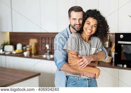 Sweet Multi-ethnic Couple In Love Stands In Embraces In The Kitchen. Cheerful An African Woman And A
