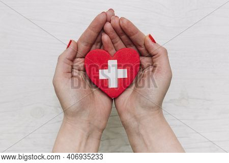 Red Heart With Cross Sign In Female Hand, Close-up