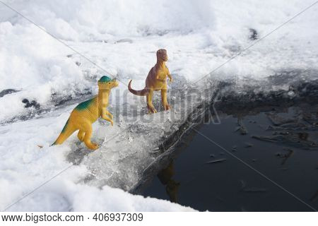 A Tyrannosaurus Dinosaur And A Pachycephalosaurus Stand On The Ice Next To The Water
