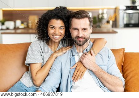 Cheerful Multi Ethnic Couple In Love Sits On The Sofa In Embraces And Looks At The Camera. A Tenderl