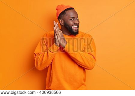 Positive Dark Skinned Man Rubs Palms And Smiles Gladfully Has Intention To Do Something Wears Hat An