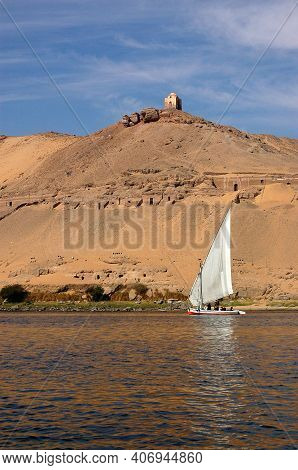 A Felucca Sails Along The River Nile Past Some Ancient Egyptian Tombs Of The Nobles (their Entrances