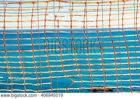 Volleyball Summer Sport Equipment. Net Netting Wire Against Blue Sea Water. Active Lifestyle.