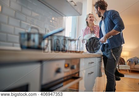 A young couple doing housework with satisfaction in a cheerful atmosphere. Kitchen, housework, home, relationship