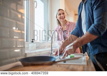 A young couple enjoying doing housework in a cheerful atmosphere in the kitchen together. Kitchen, housework, home, relationship
