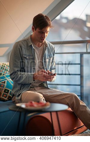A young guy chatting on the smartphone while resting in a pleasant atmosphere at home. Man, home, leisure