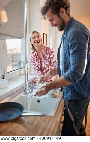 A young couple having a good time doing housework in a cheerful atmosphere in the kitchen together. Kitchen, housework, home, relationship
