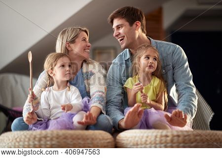 A young happy family having a good time while drumming on the furniture in a cheerful atmosphere at home together. Family, home, playing, togetherness
