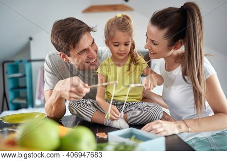 A young couple enjoying playing with their little daughter after a breakfast in a cheerful atmosphere at home. Family, breakfast, together, home