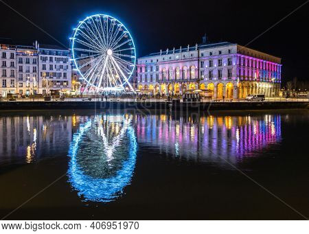 The ferris wheel and the town hall at night in Bayonne, France. Reflection on the river.