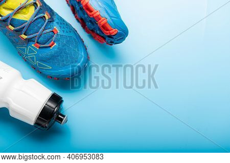 Running Shoes And A Water Bottle. Turquoise Background And Turquoise Sneakers.