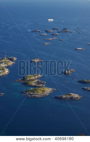 Large cruising ship passing by tiny islands on norwegian coast near town of Henningsvaer on Lofoten islands poster