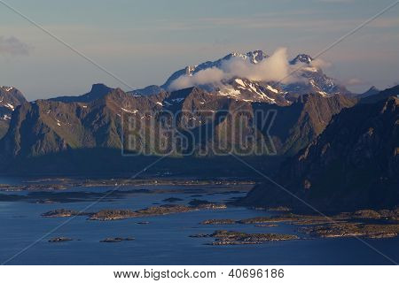 Scenic mountain peaks on Lofoten islands in Norway covered in scattered clouds with small fishing villages on the coast and rocky islands in the sea poster