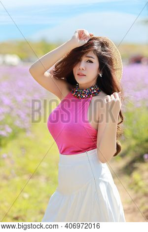 Asian Beautiful Woman, Long Hair In Cute Dress On Verbena Filed In Winter With Blue Sky. Beautiful C