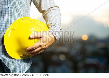 A Male Engineer With A Helmet Looking At The Future Building From The Top Of The Building In The Eve