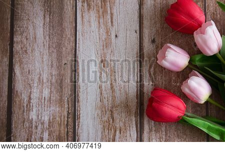 Pink And Red Tulips On A Brown Wooden Background. Background For Design. Spring Background. Mother's