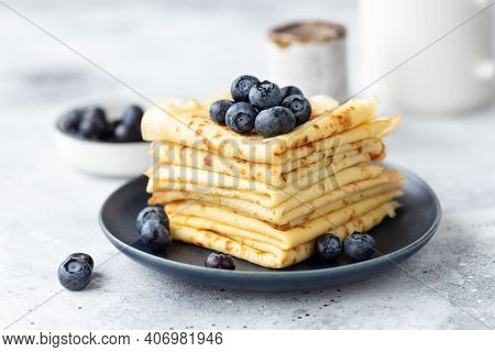 Freshly Baked Thin Pancakes, Crepes With Blueberries On Blue Plate. Healthy Breakfast. Gray Backgrou