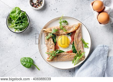 French Buckwheat Crepe With Egg, Ham And Spinach On Gray Background. Galette Bretonne. Flat Lay.