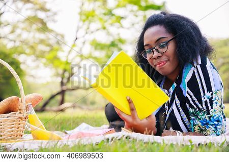 Happy Young African American Woman Reading An Interesting Book. A Cheerful African American Woman In
