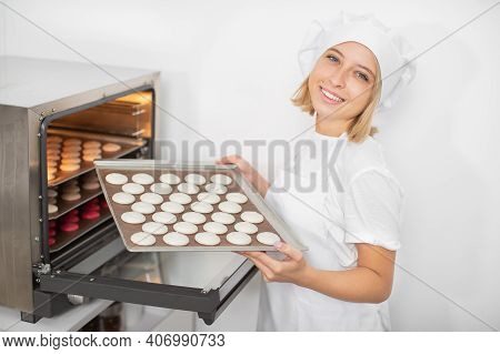 Young Cheerful Girl Confectioner In The Pastry Workshop, Holding The Baking Tray With White Macarons