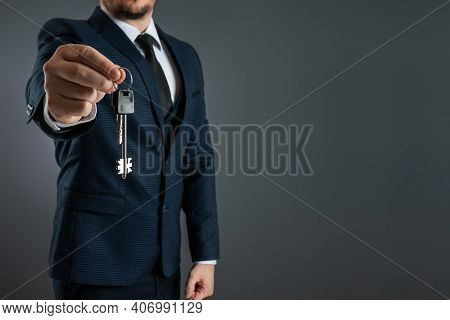 A Man In A Business Suit Holds Out The Keys In His Hand. The Concept Of A Realtor, Mortgage, Your Ho