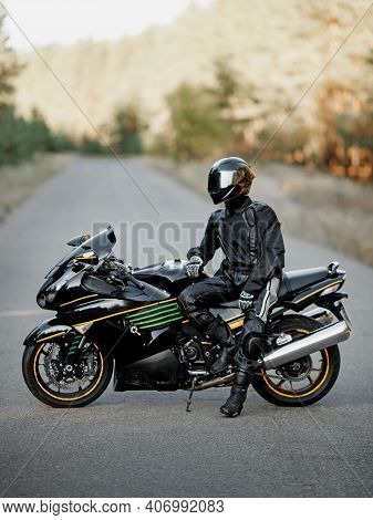 Motorcyclist In A Helmet On A Motorcycle On A Country Road. Guy Driving A Bike During A Trip. Riding