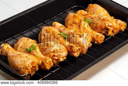 Raw Chicken Drumsticks Marinated Red With Turmeric, Garlic, Mustard And Parsley. Lined With Chicken