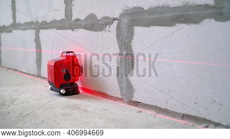 Male Tiler Put Ceramic Tiles On Wall In Bathroom, Laser Level Highlights Place Of Installation, Prof