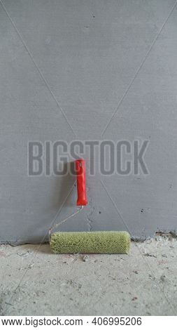 A Roller Brush With A Red Handle Stands Against A Gray Wall. Home Repairs. Wall Treatment With A Spe