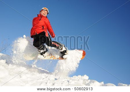 pretty young woman on the snowboard jumping over the slope in winter