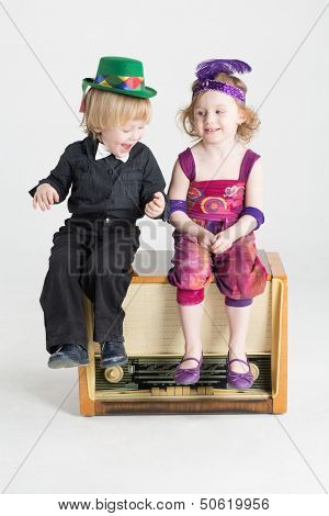 Smiling little boy and girl sitting on an old radiogramophone