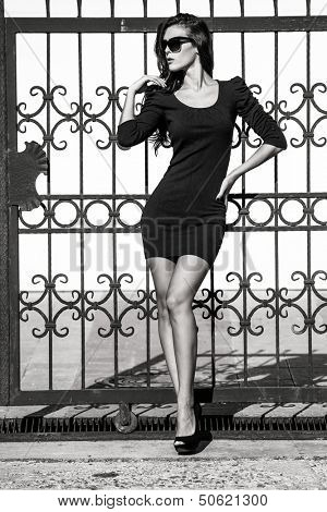 young woman in tight dress lean on wrought iron fence full body shot bw