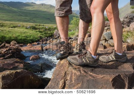 Couples feet standing at edge of river wearing hiking gear poster