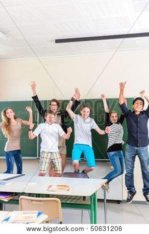 Successful Teacher and students jump in front of a blackboard with math work in a classroom or class school while lesson